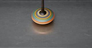 A spinning top moving on a silver surface...