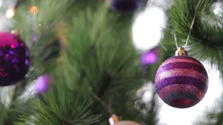 A striped purple christmas tree ball on a christmas tree