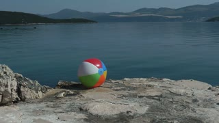 A water ball on a rock near a sea...