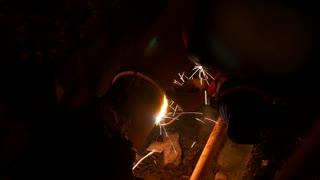 A welder in an urgent intervention, welding a ruptured heating pipe...