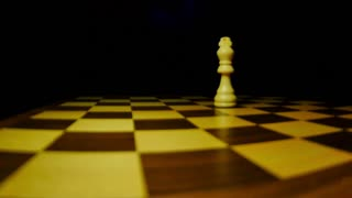 A white chess piece king standing on a chess board and a black king hits him and takes his place...