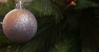 A white christmas tree ball swinging on a christmas tree