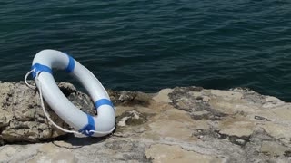 Footage of a white rescue buoy leaned on a stone and thewater flowing in the background