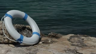 A white rescue buoy leaned on a stone near water
