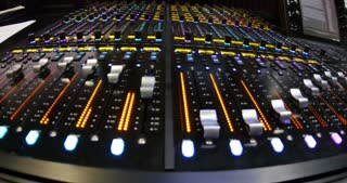 A wide angle shot of an audio mixer and a man putting it in demo mode, the knobs start to jump up and down simultaneously...