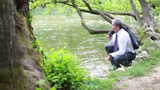 A young handsome businessman relaxing near a river and drinking water from it...