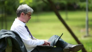 A young handsome businessman sitting on a bench and using laptop...