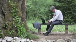 A young handsome businessman sitting on a bench, uses his laptop and receives a phone call