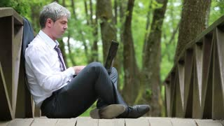A young handsome businessman sitting on a bridge and using laptop...