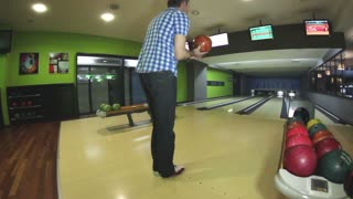 A young handsome man throws a bowling ball and... it is a strike!