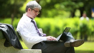 A young handsome self-confident businessman sitting on a bench in a park and using laptop