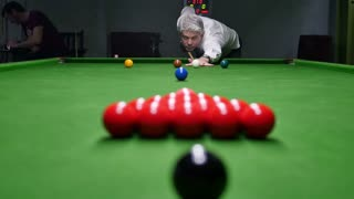 A young hansome man breaking the balls at a snooker game...
