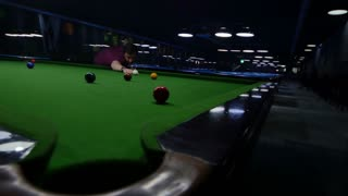A young man playing snooker in an entertainment center, he makes a point...