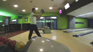 A young man throwing the bowling ball but oversteps the throwing line...