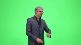 A young professor in a suit explaining and showing something on a green chroma key...