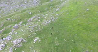 Aerial footage of a group of people hiking in the mountains...