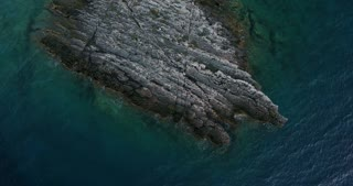 Aerial footage of a rock and the sea all around it...