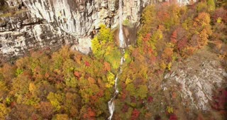 Aerial footage of an unspoiled nature, fall season and its colorful trees with a waterfall...