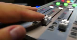 Audio mixer knobs being pulled up quickly  by a person working in a studio...