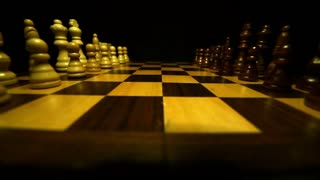 Chess figures facing each other on a chess table isolated on a black background, a person starts the game with a pawn move...