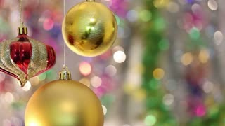 Christmas tree decorations hanging and swinging with a colorful background