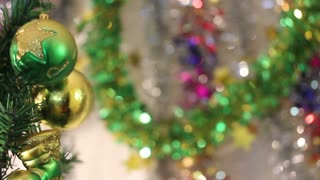 Close up footage of christmas tree decorations hanging on a christmas tree with a colorful background