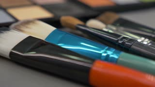 Close up and a moving shot of a make up palette and some brushes lying beside it on a table