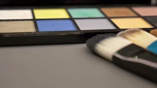 A moving shot of a make up palette and some brushes lying on a table