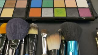Close up and a moving shot of a make up palette and some brushes lying on a table, the shot is moving from right to left...