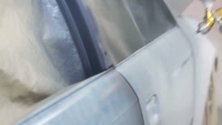 Close up footage of a car painter painting the car in a painting chamber...