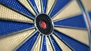 Close-up footage of a dart board and a person hitting the bullseye, in slow motion...