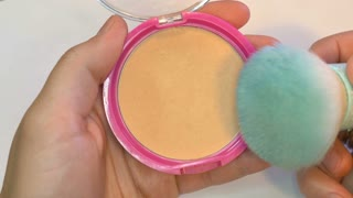 Close up footage of a make up artist showing how to take some powder with a kabuki brush...