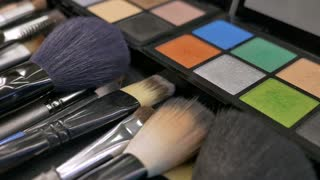 Close up footage of a make-up palette and some brushes in front of it, a person is taking the green color with a brush several times...