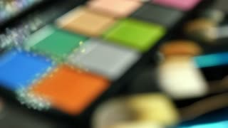 Close up footage of a make-up palette and some brushes in front of it, a person is taking the silver color with a brush several times...