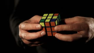 Close up footage of a man´s hands, he is solving a Rubik´s cube, isolated on a black background