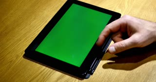Close up footage of a person leafs through a tablet, the background on the device is the chroma key