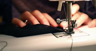 Close up footage of a woman sewing a black cotton with a sewing machine