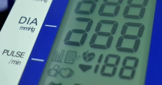 Close-up footage of an electric device and a person measuring heartrate and blood pressure...