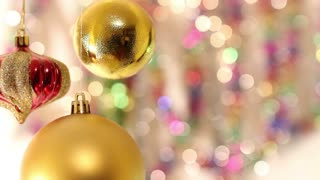 Close up footage of several colorful christmas tree decorations hanging and swinging with a colorful background
