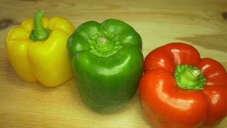 Close up footage of three paprika of different color lying on a wooden table, the table rotates and brings the vegetables into frame