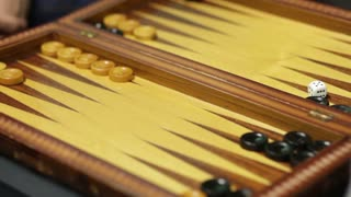 Close up footage of two players playing backgammon
