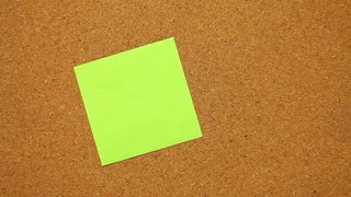 Close-up of a human hand that writes ˝It´s lunch time˝ on a post-it paper...