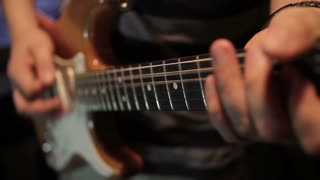 Close up shot, in a recording studio and a man playing on his electric guitar...