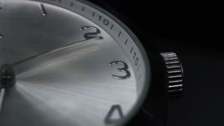 Close up shot of a clock and its seconds hand isolated on a black background showing the time passing...