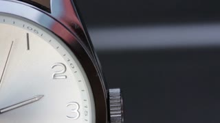 Close up shot of a clock and its seconds hand - the shot moves from up to the bottom of the clock