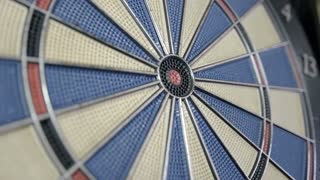 Close-up shot of a dart board and a person hits the bullseye...