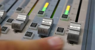 Close up shot of a person adjusting the volume on an audio mixer...