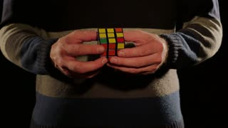 Close up shot of a person solving the Rubik´s cube, isolated on a black background