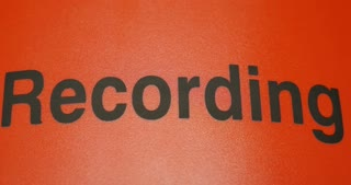 Close up shot of a recording sign, the shot goes into focus and out of focus