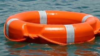 Close up shot of a red rescue buoy floating on the water surface